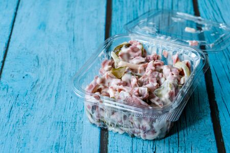 Take Away Appetizer Italian Salad with Mayonnaise, Ham and Pickle in Plastic Box Container. Traditional Dish.