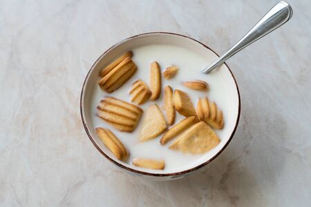 Baby Biscuits with Milk in Bowl also for Theeting. Ready to Eat. Archivio Fotografico