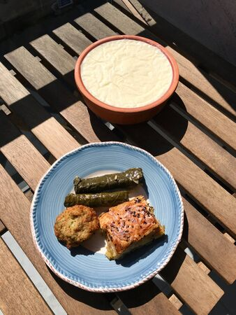 Traditional Turkish Food Stuffed Grape Leaves Dolma, Borek / Burek and Mucver also called Fried Zucchini Balls with Homemade Yogurt / Yoghurt in Clay Pot on Wooden Table. Organic Food.