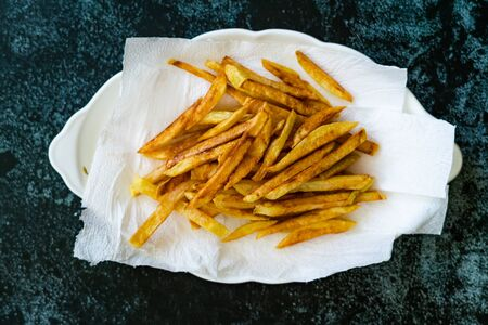Cajun Seasoned Skinny French Fries Potatoes in Plate with Paper Towels. Ready to Serve Homemade Food.