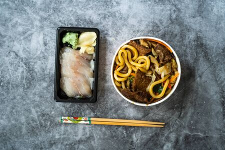 Take Away Asian Food Menu Set with Beef Udon Noodle Soup and Raw Fish Sashimi served with Pickled Ginger and Wasabi.