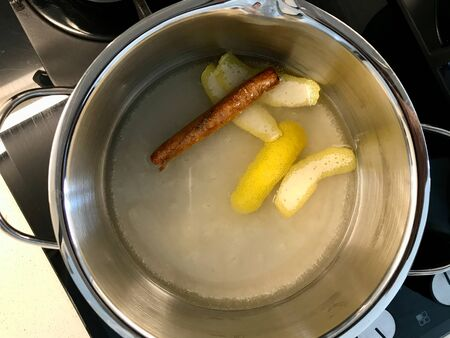 Making Sherbet with Cinnamon Stick, Lemon Peel and Water in Pot for Pasteis de Nata or Belem Tart. Portuguese Custard made with Egg, Cinnamon, Sugar and Flour. Traditional Dessert. Stock Photo