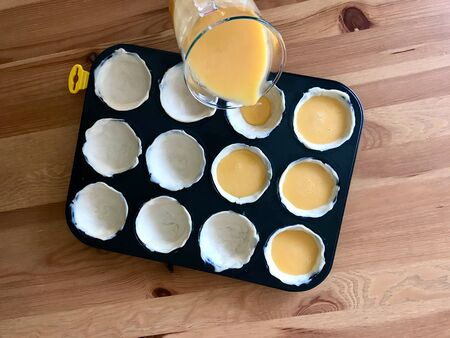 Making and Cooking Pasteis de Nata or Belem Tart. Portuguese Custard made with Egg, Cinnamon, Sugar and Flour in Muffin Tray / Cupcake Mold. Traditional Dessert.