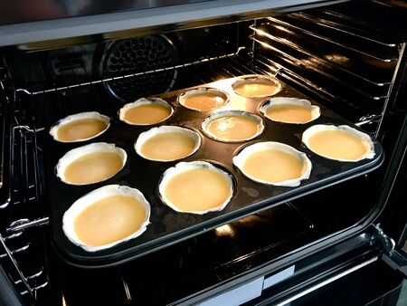 Making and Cooking Pasteis de Nata or Belem Tart. Portuguese Custard made with Egg, Cinnamon, Sugar and Flour in Muffin Tray / Cupcake Mold in Oven. Traditional Dessert.