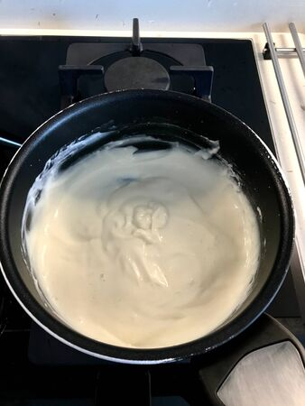 Making and Cooking Cream in Pot For Pasteis de Nata or Belem Tart. Portuguese Custard made with Egg, Cinnamon, Sugar and Flour. Traditional Dessert. Stock Photo