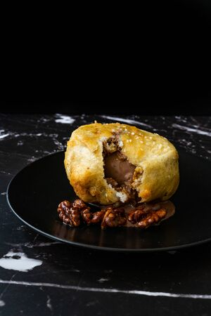 Fried Ice Cream with Chocolate and Roasted Walnuts in Dark Black Plate. Traditional Organic Dessert. Stock Photo