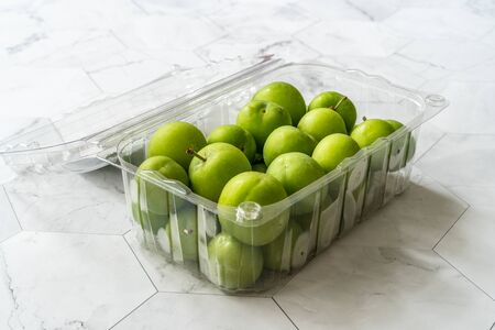 Raw Organic Sour Green Plums for Sale Ready to Eat in Plastic Container Box Package. Healthy Food.