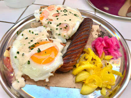 American Style Breakfast Croque Madame with Sausage, Pickled Turmeric Onions and Pickle. Fast food.