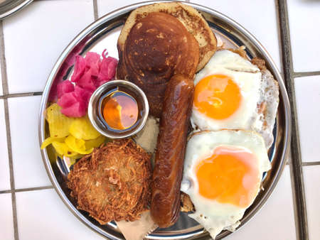 American Breakfast with Pancake Maple Syrup, Sunny Side Up Eggs, Hash Brown, Sausage, Turmeric Pickled Onions and Pickle. Traditional Fast Food. 版權商用圖片