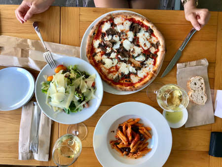 Italian Food Table with Penne Pasta, Funghi Mushroom Pizza, Parmesan Cheese Salad and White Wine at Local Restaurant. Ready to Eat.