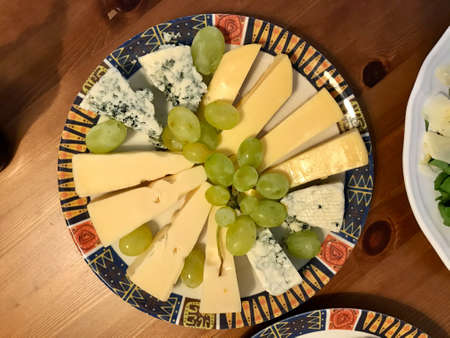 Tasty Cheese Plate with Roquefort Blue Holland Cheese and Green Grape. Ready to Eat and Serve.