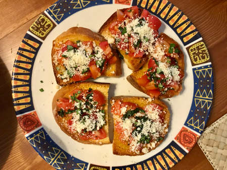 Homemade Tasty Savory Tomato Italian Appetizers, or Bruschetta, on slices of Toasted Baguette. Healthy Organic Traditional Food.