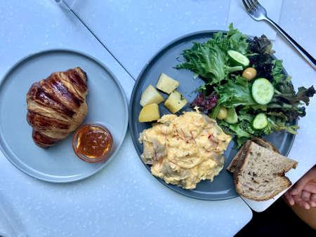 Breakfast Plate with Scrambled Egg, Mushroom, Croissant, Sourdough Bread and Salad at Cafe Restaurant.