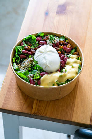Healthy Organic Take Away Food Bowl with Burrata Cheese, Mexican Beans, Amaranth Seeds, Three Color Quinoa and Mixed Leaves. Ready to Deliver and Serve.