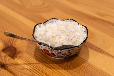 Grated Parmesan Cheese in Bowl on Wooden Surface at Kitchen. Traditional Organic Food.