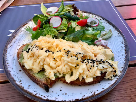 Scrambled Egg with Avocado Smash on Bread and Salad for Breakfast. Healthy Organic Food.