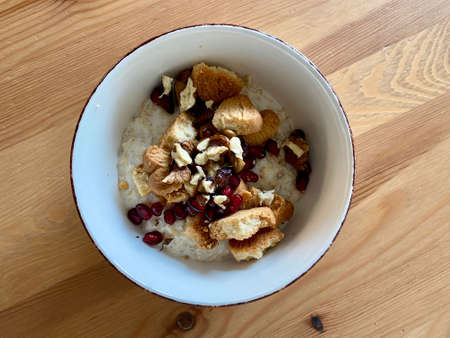 Oatmeal Porridge Bowl with Biscuit, Apple slices, Pomegranate Seeds and Walnut. Ready to Eat and Serve.
