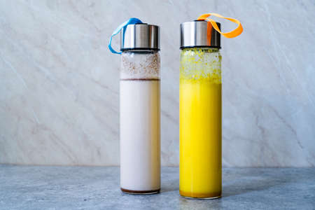 Take Away Homemade Almond Milk and Golden Milk in Bottle with Vanilla Extract and Cinnamon Powder. Ready to Drink.