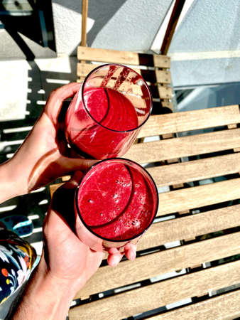 Acai Smoothie with Beetroot and Beet Cheers Outside Sunny Day with Friends. Ready to Drink.