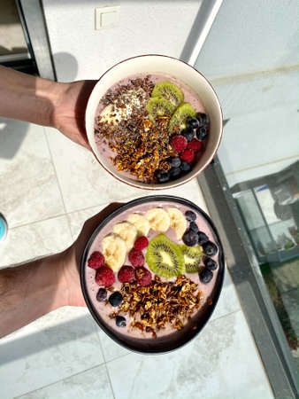 Acai Smoothie Bowl with Baked Granola, Blueberries, Raspberry, Banana and Kiwi in Hand. Ready to Serve and Eat.