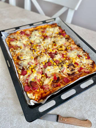 Homemade Freshly Baked Pizza in Baking Tray with Pepperoni, Mozzarella Cheese, Sausage and Corn. Ready to Eat. Imagens
