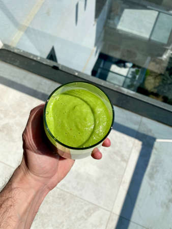 Refreshing Green Smoothie with Avocado and Spinach Holding in Hand Outside Hot Sunny Weather. Ready to Drink.