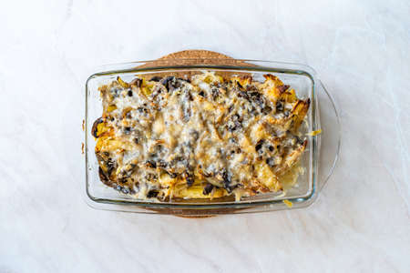 Baked Potatoes with Mushrooms and Parmesan Cheese Casserole in Glass Bowl. Ready to Serve and Eat.