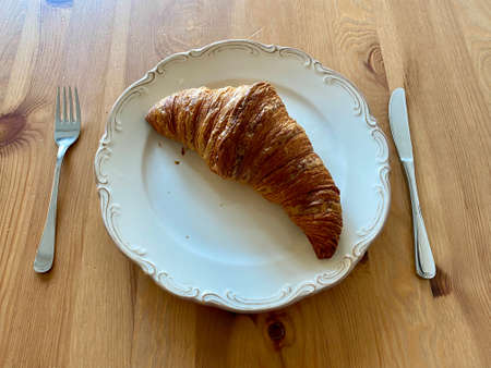 Croissant in Plate served with Knife and Fork for Breakfast on Wooden Table. Ready to Eat.