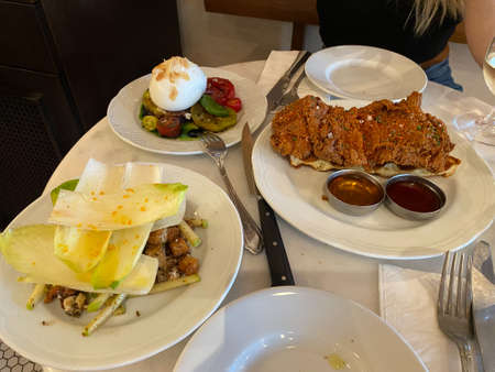 Crispy Chicken with Waffle, Lettuce Salad and Burrata Cheese served at Restaurant. Ready to Eat. Stock Photo