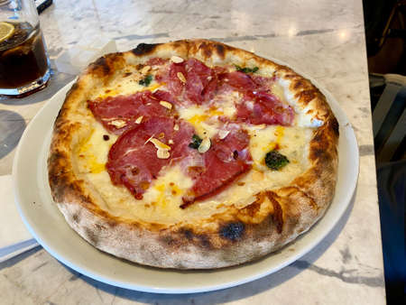Pizza with bacon, pepperoni, melted cheese, olives served at Local Restaurant. Ready to Serve.