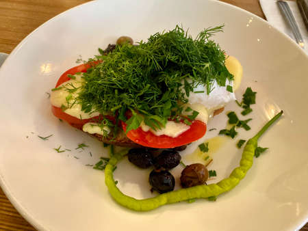 Healthy Breakfast Plate Tartine with Dill, Poached Egg and Green Pepper served at Restaurant. ready to eat.