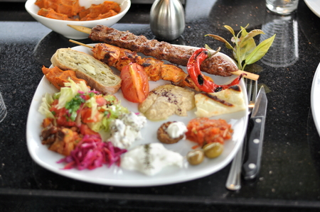 Traditional Cypriot meze and mix meat and chicken kebab table with charcoal barbecue on the table for self cooking during the eating time