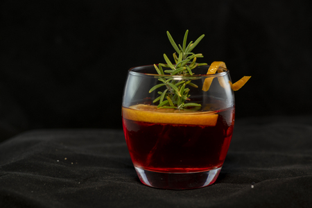 Gotfather cocktail with bourbon whiskey, amaretto, orange wedge and rosemary with isolated black background
