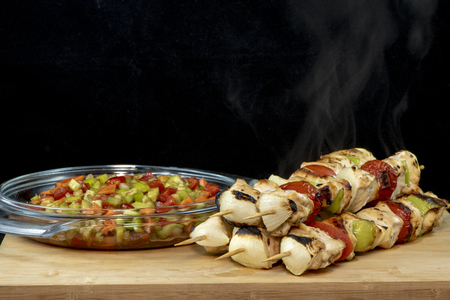 Chicken Shish Kebab with tomato, onion and green peppers on wood with isolated black background