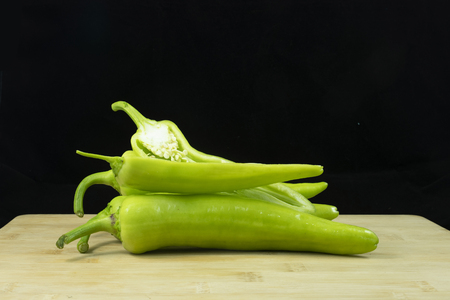 Fresh green peppers with banana shape on wood with isolated black background