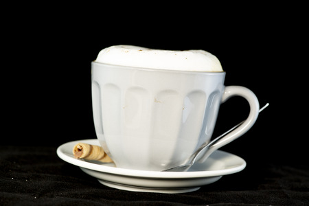 Delicious Cappuccino served with chocolate hazelnut wafer roll isolated black background