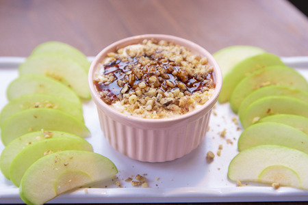 Caramel Apple Dip with nuts, caramel dressing and fresh apple slices on wood
