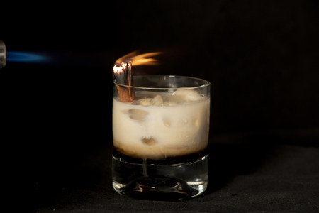 Flaming Cinnamon cocktail with coffee flavor alcohol,  irish cream and sambuca with isolated black background