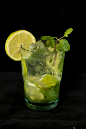 Mojito Cocktail with rum, brown sugar, lemon juice, mint and soda water with isolated black background 스톡 콘텐츠