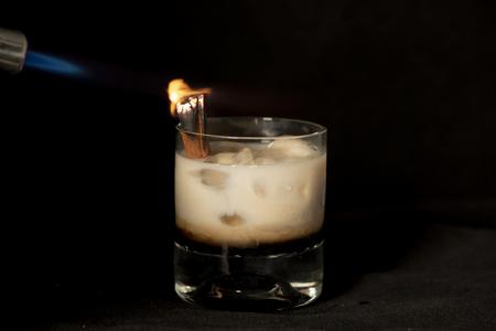 Flaming Cinnamon cocktail irish cream and sambuca with isolated black background Foto de archivo