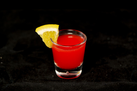 Redheaded Slut cocktail, cranberry juice and peach schnapps with isolated black background
