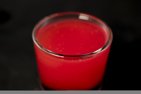Red shot cocktail , cranberry juice and schnapps with isolated black background