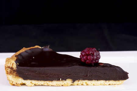 Fresh baked chocolate tart with raspberry on top served on white plate with isolated black background