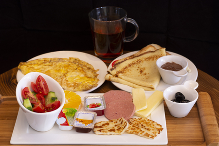 Traditional Turkish breakfast with omelette, pancake, tea, fruits and breakfast foods