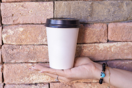 Take away coffee mug on the hand with brick wall background