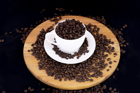 Coffee beans inside the coffee mug on wood with isolated black background