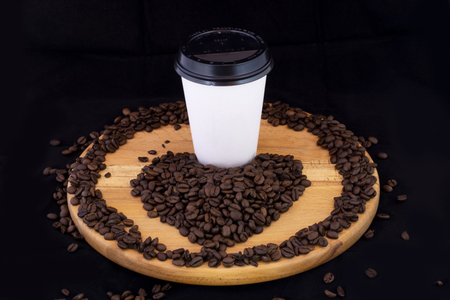 Take away coffee cartoon and coffee beans on wood with isolated black background
