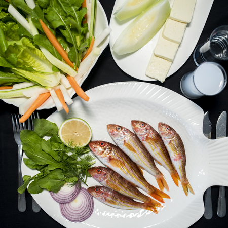 Fresh red mullet fishes with green salad, feta cheese, melon and Turkish alcoholic drink raki
