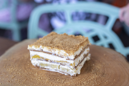 Delicious mango float cake on wood plate 스톡 콘텐츠