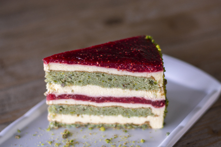 Pistachio and berry cake on white plate on wood table